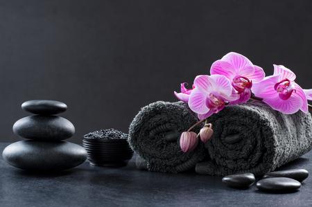 Zwarte spa-omgeving met grijze handdoeken, hete stenen en prachtige orchideeën. Kuuroord en wellnessachtergrond met stapel hete stenen met roze bloemen op bord. Luxury spa samenstelling en ontspannen concept.