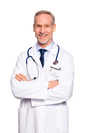 Portrait of happy senior doctor with folded arms isolated on white background. Confident male doctor in a labcoat and stethoscope looking at camera. Portrait of handsome mature doctor. 스톡 콘텐츠
