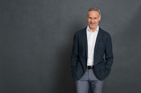 Happy senior businessman wearing suit standing over grey wall and looking at camera. Portrait of successful leader standing isolated gray background with copy space. Handsome mature man with fashion clothes.