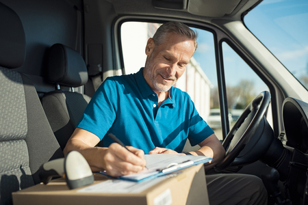 Happy delivery man with cardboard box checking list in van. Smiling courier checking list on clipboard. Deliveryman sitting in van and checking the delivery list. Banque d'images