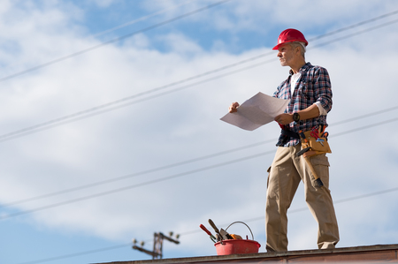 Engineer standing on rooftop looking away and holding blueprint project. Mature construction worker kit standing on rooftop with copy space. Workman inspecting construction site with sheet of paper in hand.