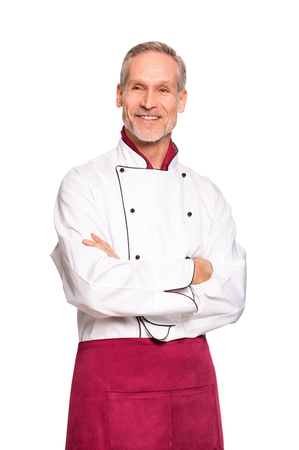 Chef professionnel confiant avec les mains croisées isolé sur fond blanc. Heureux cuisinier mature avec tablier rouge et uniforme blanc. Portrait de l'homme chef satisfait avec bras croisés en détournant les yeux. Banque d'images