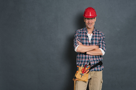 Successful bricklayer with red helmet and equipment tool kit on waist standing against grey wall. Portrait of happy manual worker isolated over grey background. Satisfied mature craftsman with copy space.