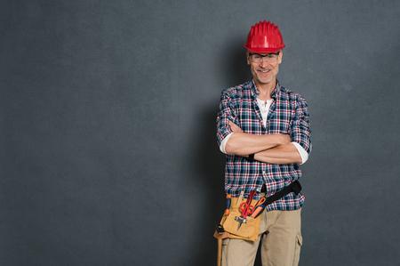 Succesvolle metselaar met rode helm en apparatuurhulpmiddeluitrusting op taille die zich tegen grijze muur bevinden. Portret van gelukkige handarbeider die over grijze achtergrond wordt geïsoleerd. Tevreden rijpe vakman met exemplaarruimte.