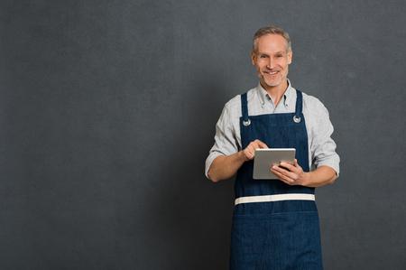 Homme souriant à l'aide de tablette numérique pour son entreprise isolé sur fond gris. Portrait d'un homme mature heureux en tablier bleu isolé sur mur gris. Propriétaire d'entreprise satisfait prendre des commandes sur tablette numérique et en regardant la caméra.