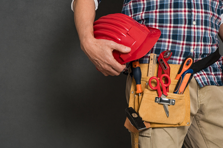 Closeup of hardhat held by construction worker on grey background. Detail of bricklayer holding red helmet and kit tool. Closeup of craftsman hand holding tool belt with equipment on grey wall with copy space.