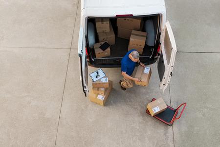 Entregador, segurando a caixa de papelão e descarga de encomendas para entrega. Vista superior do correio que descarrega pacotes da camionete. Alto, ângulo, vista, homem, removendo, pacotes, entrega
