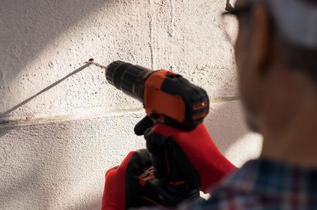 Sluit omhoog de hand van de bouwvakker gebruikend elektrische boor makend gat in muur. Detail van metselaarhanden die boormachine houden en aan bouwterrein werken. Bouwer die een gat in de muur van een nieuw gebouw boort.