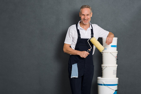 Smiling painter holding a paint roller and leaning on stack of paint bucket. Portrait of happy mature painter looking at camera isolated over grey wall. Satisfied handyman with roller and paint bucket with copy space.