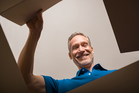 Happy mature man looking into parcel cardboard box and smiling. Cheerful senior man happy on seeing package. Smiling man feeling overjoyed on seeing parcel and opening it. Banco de Imagens