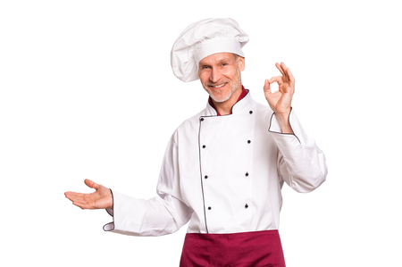 Smiling senior cook showing something isolated on white background. Portrait of happy mature chef presenting over white background. Cheerful chef man looking at camera isolated on white with hand sign ok.