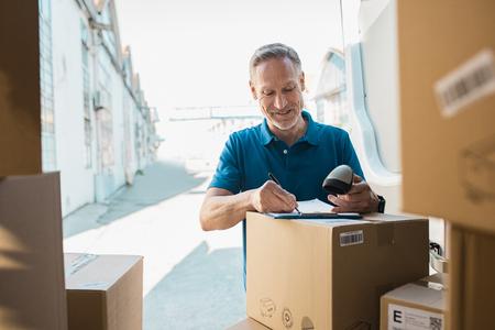 Livreur, signature, liste de contrôle, et, tenue, scanner, main Courrier heureux écrit sur le presse-papiers et le code-barres de numérisation. Homme d'âge mûr mise à jour de la liste de vérification de la livraison en fourgonnette.
