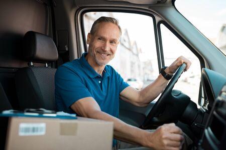 Livreur conduite van avec des paquets sur le siège avant. Courrier adulte heureux en camion. Portrait de courrier express confiant au volant de sa camionnette de livraison. Banque d'images