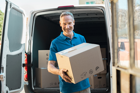 Proud delivery man in blue uniform holding parcel and looking at camera. Smiling mature courier standing in front of cargo van delivering package. Portrait of delivery man holding card box. Banque d'images