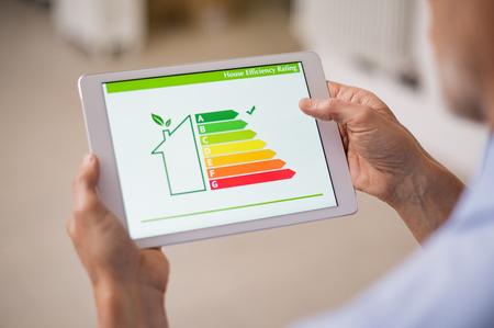 Hand, die digitale Tablette hält und Hauseffizienzbewertung betrachtet. Detail der Hauseffizienzbewertung auf digitalem Tablettenschirm. Konzept des ökologischen und bioenergetischen Hauses. Energieklasse. Standard-Bild