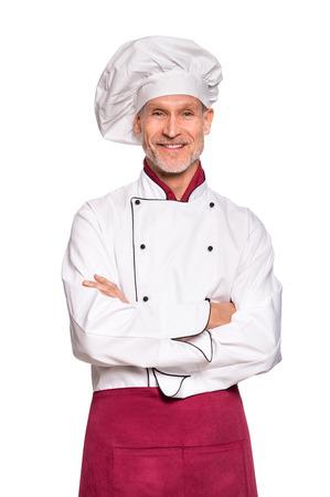 Restaurant expérimenté chef debout avec les bras croisés isolé sur fond blanc. Cuisinier professionnel debout en tablier uniforme et rouge blanc. Portrait du chef heureux et réussie avec capuchon en regardant la caméra.