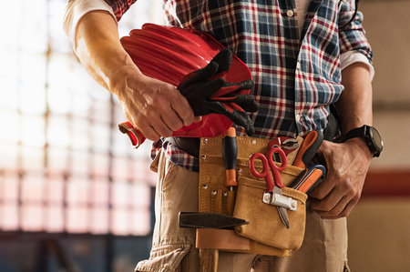 Closeup of bricklayer hands holding hardhat and construction equipment. Detail of mason man hands holding work gloves and wearing tool kit on waist. Handyman with tools belt and artisan equipment.