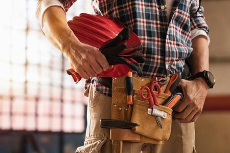 Nahaufnahme von Maurerhänden, die Hardhat und Baugeräte halten. Detail von Maurermannhänden, die Arbeitshandschuhe halten und Werkzeugausrüstung auf Taille tragen. Heimwerker mit Werkzeuggurt und Handwerkerausrüstung.