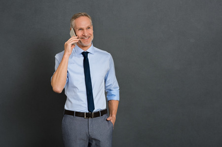 Senior businessman talking over phone and looking away isolated on gray background. Happy mature business man using smartphone. Portrait of smiling leader on his cellphone thinking with copy space.