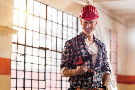 Dojrzały murarz trzyma wiertarkę elektryczną na placu budowy. Zadowolony murarz z czerwonym kaskiem patrząc na kamery na budowie. Portret dojrzały robotnik z narzędzia budowlanego. Zdjęcie Seryjne