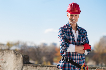 Smiling craftsman standing with arms folded and looking at camera. Happy construction worker with tool kit on waist and work gloves standing on rooftop. Portrait of satisfied bricklayer with copy space.