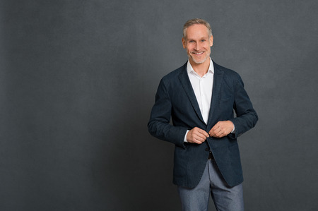 Happy senior businessman adjusting suit button and looking at camera. Handsome mature man looking at camera isolated on grey wall with copy space. Successful executive in fashion clothes smiling.