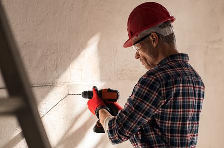 Travailleur de la construction faisant le trou dans le mur avec une perceuse électrique. Bricklayer trou de forage dans le mur dans un chantier de construction. Homme mûr portant un casque faisant un trou dans le mur pour les travaux d'entretien. Banque d'images