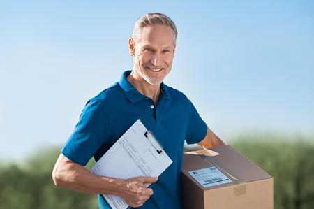 Livreur souriant tenant le paquet et la facture. Facteur en uniforme bleu tenant des colis et en regardant la caméra. Heureux homme de messagerie tenant une boîte en carton et un presse-papiers avec accusé de réception. Banque d'images