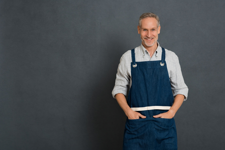 Mature small business owner standing and looking at camera isolated on grey wall. Happy man in work clothes with apron standing. Portrait of successful owner smiling with copy space. 版權商用圖片