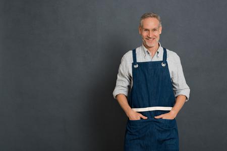 Propriétaire de petite entreprise mature debout et regardant la caméra isolée sur un mur gris. Homme heureux dans les vêtements de travail avec tablier permanent. Portrait du propriétaire réussi, souriant avec espace copie.