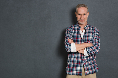 Portrait of senior man standing with arms crossed in smart casual clothing against a grey wall. Satisfied mature craftsman smiling isolated on grey background. Successful worker looking at camera with copy space. Banque d'images