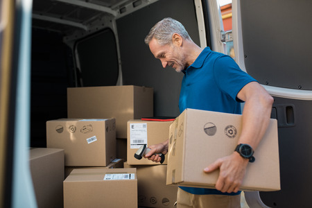 Delivery man scanning cardboard boxes with barcode scanner. Courier holding parcel and scanning barcode with barcode reader in van. Mature man reading and scanning labels on boxes before shipment. Banque d'images