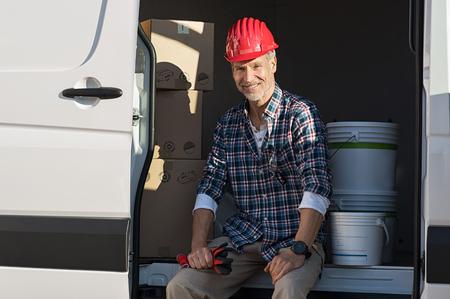 Heureux artisan mature assis dans une camionnette avec boîte en carton et des seaux de peinture. Homme mûr souriant avec casque et gants de travail prêts pour le travail. Portrait de peintre assis avec boîte dans la camionnette pour le déménagement.