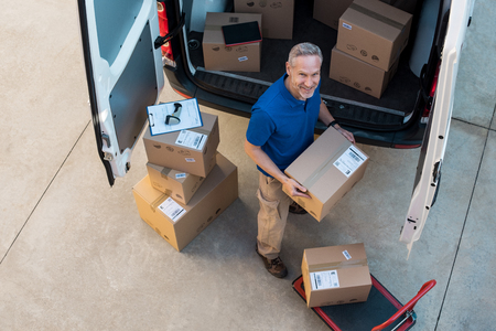 Happy delivery man holding cardboard package and looking at camera. Top view of courier loading packages in van for delivery. Portrait of happy man working at courier service and carrying parcels outside van. Stock fotó
