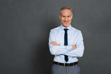 Happy senior businessman in blue shirt and tie with arms crossed looking at camera. Smiling and satisfied business man isolated over grey background. Senior manager in formal standing with copy space.