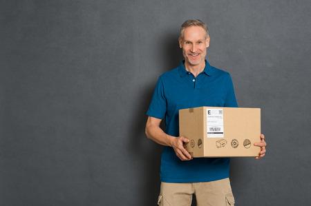 Corriere felice che tiene scatola di cartone e che guarda l'obbiettivo. Fattorino sorridente che tiene e che porta una scatola di carta isolata su fondo grigio. Ritratto del pacchetto della tenuta del fattorino con lo spazio della copia isolato.