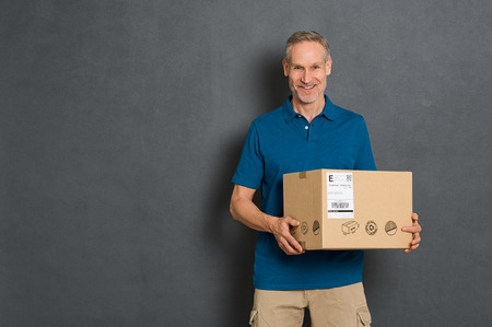 Happy courier holding cardboard box and looking at camera. Smiling delivery man holding and carrying a card box isolated on grey background. Portrait of deliveryman holding parcel with copy space isolated. Banque d'images
