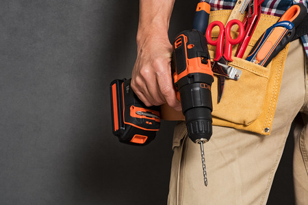 Close up of handyman holding a drill machine with tool belt around waist. Detail of artisan hand holding electric drill with tools isolated over grey background. Closeup hand of bricklayer holding carpentry accessories.