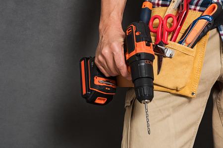 Feche de trabalhador manual segurando uma máquina de broca com cinto de ferramentas na cintura. Detalhe de mão do artesão que guarda a broca elétrica com as ferramentas isoladas sobre o fundo cinzento. Mão do close up do pedreiro que guarda acessórios da carpintaria.