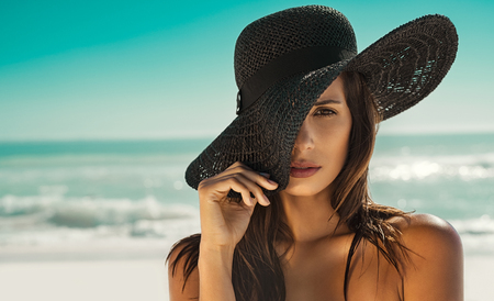 Portrait of fashion young woman posing against sea wearing a black straw hat. Sensual girl covering half face with hat on beach with copy space. Attractive girl looking at camera with sea in background.