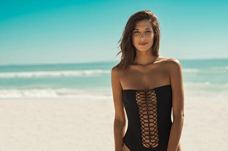 Femme belle mode en maillot de bain noir regardant la caméra. Portrait d'une fille sensuelle en maillot de bain noir debout sur une plage tropicale. Portrait de femme bronzée sexy marchant sur la plage. Banque d'images - 97293184