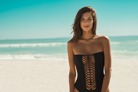 Beautiful fashion woman in black swimsuit looking at camera. Portrait of sensual girl in black swimwear standing on tropical beach. Portrait of sexy tanned woman walking at beach.