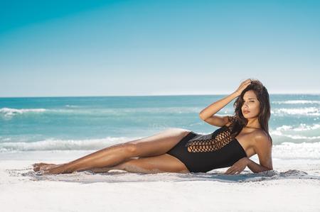 Femme Fashion en maillot de bain noir allongé sur la plage tropicale. Portrait de la belle jeune femme allongée sur le côté en profitant d'un bain de soleil près du bord de mer. Fille bronzée sexy en maillot de bain élégant en regardant la caméra.