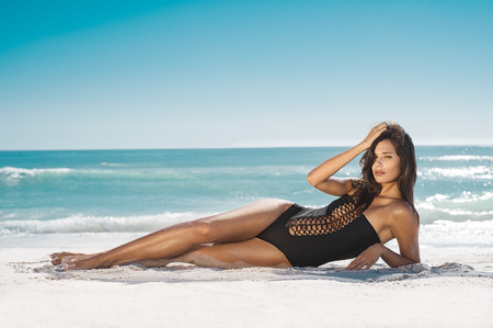 Mujer de moda en traje de baño negro tumbado en la playa tropical. Retrato de hermosa mujer joven tumbado en el lado disfrutando del sol cerca de la orilla del mar. Chica bronceada sexy en elegante traje de baño mirando a cámara.