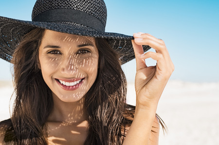 Portrait of beautiful young woman wearing summer black hat with large brim at beach. Closeup face of attractive girl with black straw hat. Happy latin woman smiling and looking at camera with sea in background. Stock Photo