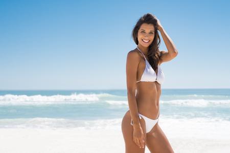Portret van jonge vrouw in witte bikini op tropisch strand die camera bekijken. Mooi Latijns meisje in badmode met kopie ruimte. Zomervakantie en zonnebank concept.