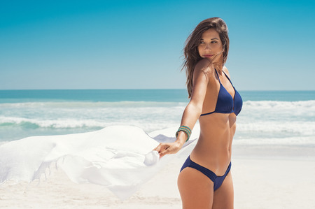 Young woman waving white scarf in wind at beach. Latin happy girl in blue bikini holding tissue and looking away at sea. Sexy fashion woman playing with the scarf on seashore.  스톡 콘텐츠