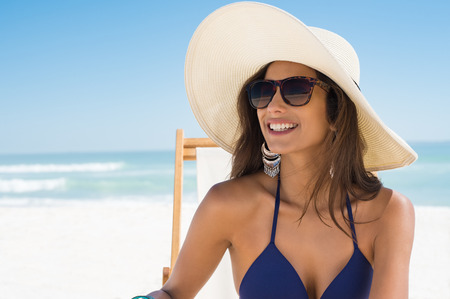 Young woman in blue bikini sitting on deck chair wearing white straw hat. Happy girl enjoying summer vacation at beach. Portrait of beautiful latin woman relaxing at beach with sunglasses looking away. Archivio Fotografico