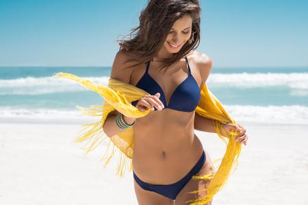 Bella giovane donna che funziona sulla spiaggia con un tessuto giallo. Ragazza sorridente felice con la sciarpa che gode in spiaggia. Libertà e concetto spensierato.