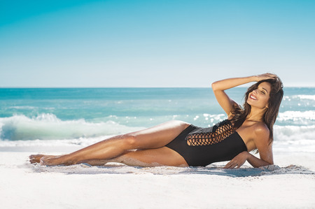 Happy young woman in black swimwear enjoying vacation on beach. Portrait of tanned girl lying on side and looking at camera while smiling. Beautiful and sexy girl enjoying sunbathing during summer.